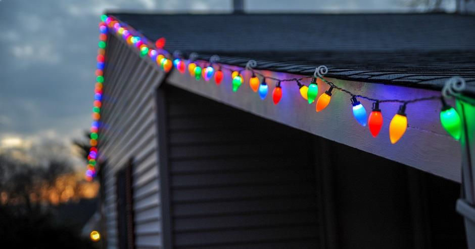Close-up view of a house with multi-colored holiday lights