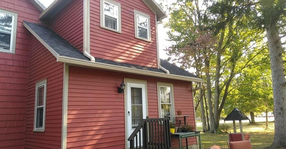 Front view of a house with red siding and a K-Guard Leaf Free Gutter System
